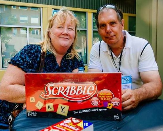 Photo of two lucky geocachers who won the Scrabble board game and Scrabble Dictionary at the 2014 Geocaching Block Party