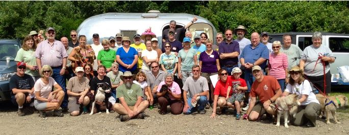 Group photo from the Silver Bullet geocaching event in front of the renovateda 1964 Airstream Bambi II trailer