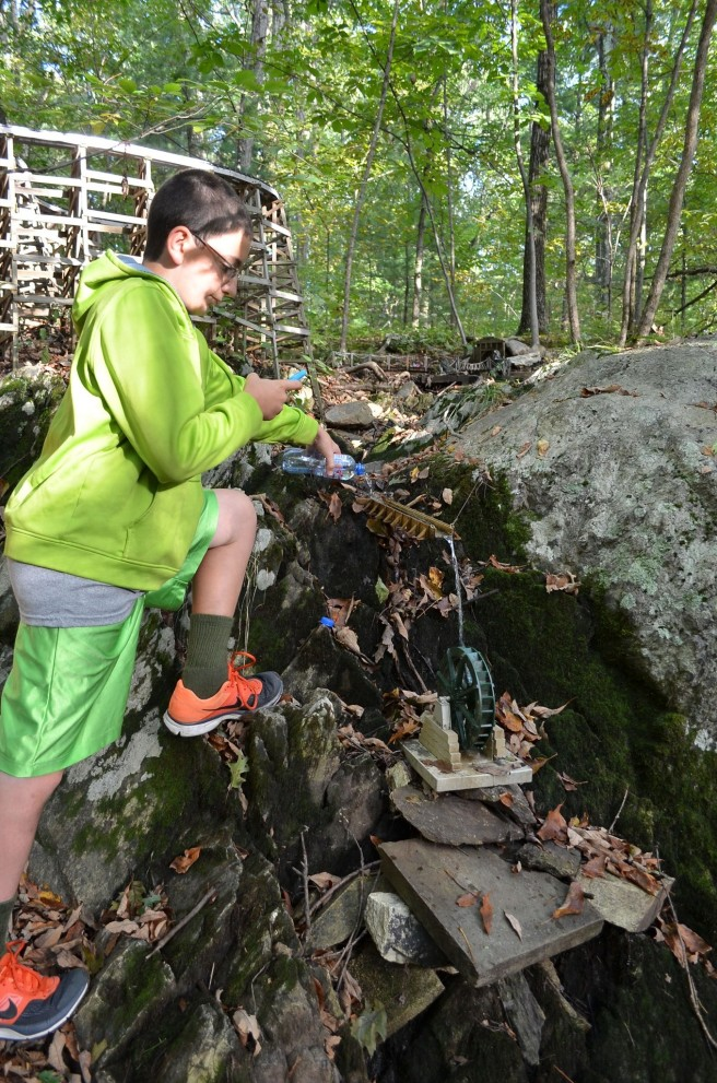 A young geocacher testing out the waterfall and waterwheel.