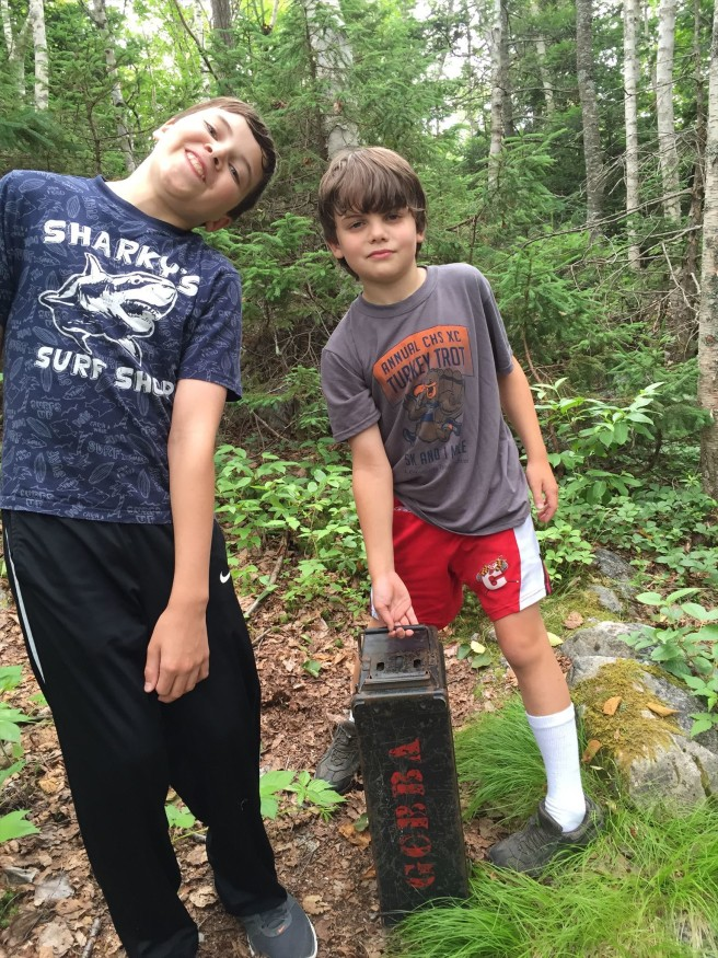 "Says lpaulriddle: ""My always-photogenic kids posing with GCBBA, Canada's oldest geocache."""