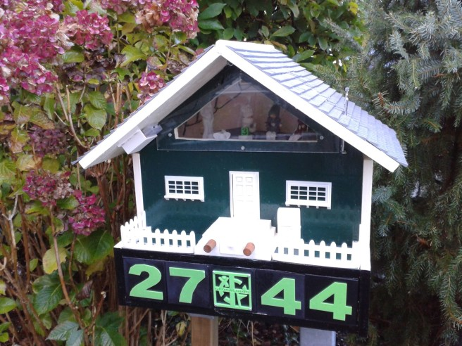 The cache is disguised as a birdhouse displaying the CO's street number.